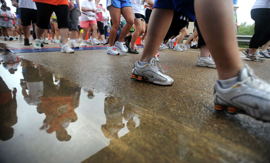 Despite the heavy mist and light rain competitors in the first Gusher Marathon take off at the Montagne Center in Beaumont, Saturday. Tammy McKinley/ The Enterprise