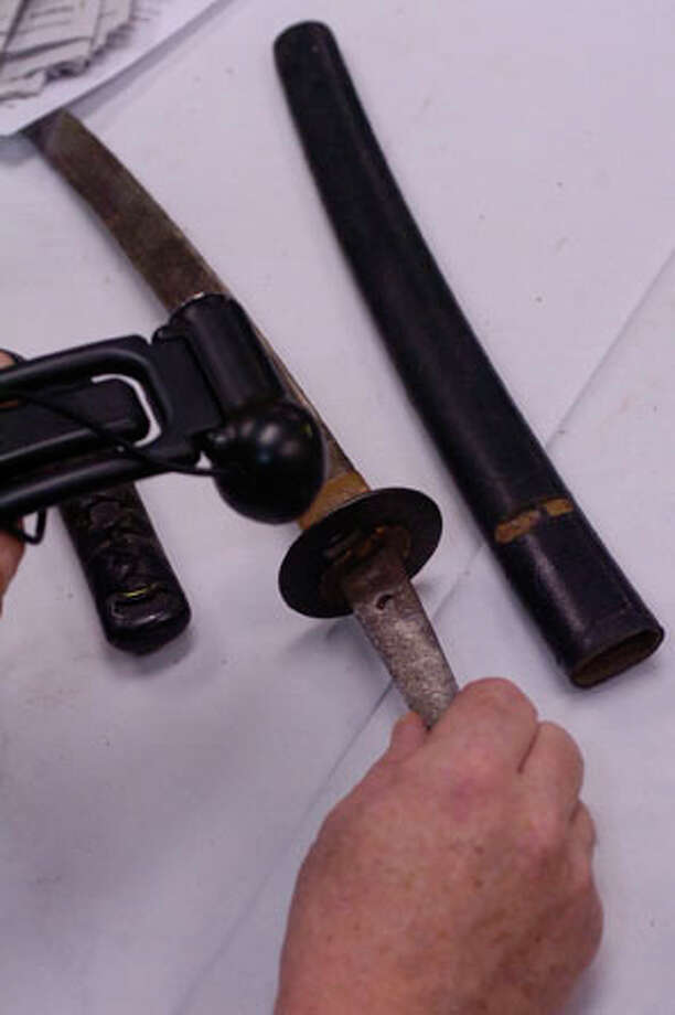 The Great Treasure Hunt is in Beaumont through this week.  Vince Pitti, one of the appraisers, uses a small camera to send writing to his headquarters about this  WW II Japanese short sword.  Dave Ryan/The Enterprise