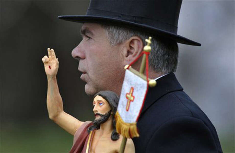 Johannes Wessela carries the figure of Jesus during the Easter riders' procession in Crostwitz, eastern Germany, Sunday. According to a tradition more than a century old, men of the Sorbs, dressed in black tailcoats riding on decorated horses, proclaim, singing and praying, the message of Jesus resurrection. (AP Photo/Matthias Rietschel) / DAPD