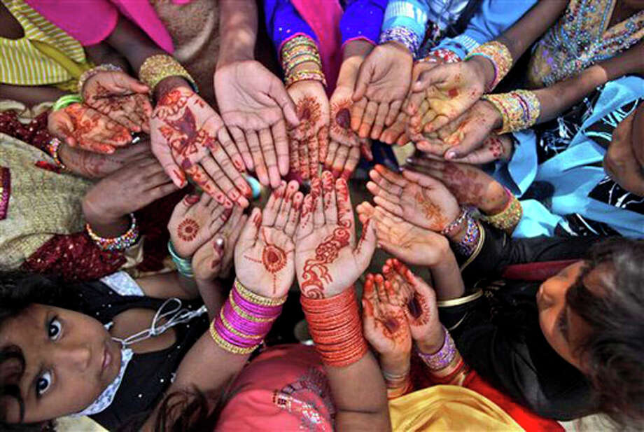 A Pakistani Christian girl, bottom left, looks up while she and other girls display their hands decorated with bangles and painted with Henna paste as they celebrate Easter holiday after a mass at a church in a Christian neighborhood of Islamabad, Pakistan. Pakistani Christians account for about 3.8 million of Pakistan's 140 million people. (AP Photo/Muhammed Muheisen) / AP