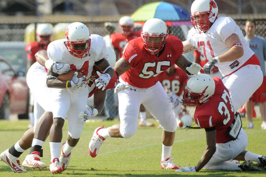 Lamar wide receiver Van Franks, left, tries to break a tackle during the Cardinals first of three spring practice scrimmages at Vernon Glass Field of Champions. Friday, March 26,  2010. Valentino Mauricio/The Enterprise