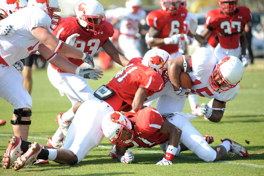 Lamar running back Cornelius Shackelford, right, tries to plow through the defense during a spring practice. Valentino Mauricio/The Enterprise