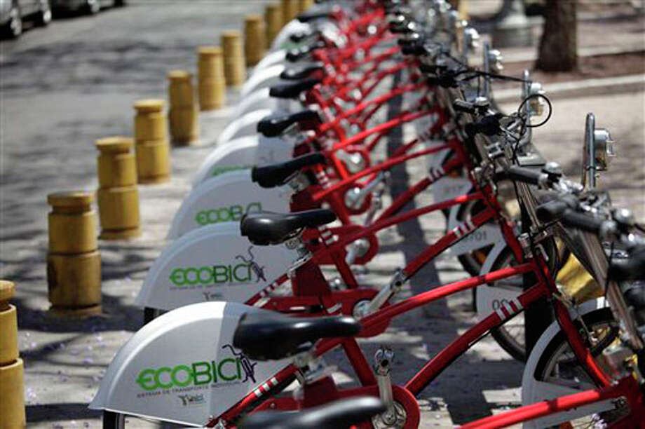 """Bicycles are lined up at an """"Ecobici"""" station in Mexico City. This spring, the city government launched """"Ecobici,"""" a bike sharing program, installing 1,100 bikes at 85 stations throughout the downtown area. AP Photo/Dario Lopez-Mills / AP"""