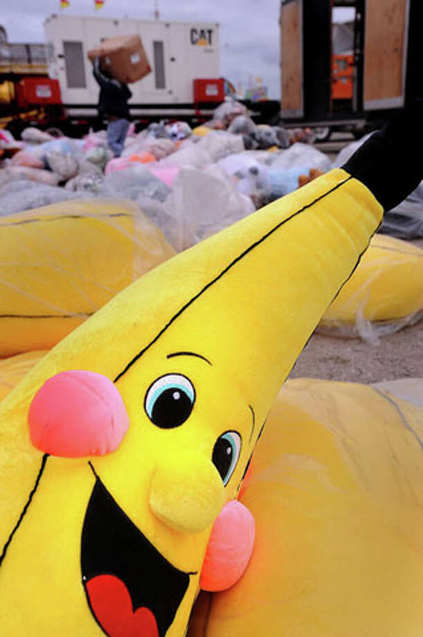John Harris hauls a box through a field of stuffed animals during preparation for Thursday's opening the South Texas State Fair. A smiley banana waits to be won as a prize.  Guiseppe Barranco/The Enterprise
