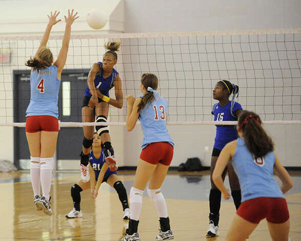 Ozen's A'Lexus Brannon drives a spike past Lumberton blocker Kindell Johnston (4) during District 20-4A volleyball action at Ozen High School on September 22, 2009. Valentino Mauricio/The Enterprise / Beaumont