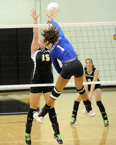 Ozen's Alexis Brannon (1) spikes the ball past  Nederland's Cassie Hyde (15) during District 20-4A play in September. Valentino Mauricio/The Enterprise / Beaumont