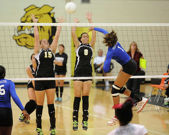 Ozen's A'Lexus Brannon (1) spikes the ball past  Nederland's Cassie Hyde (15) and Jordi LeBouef (8) during District 20-4A play in September 2009. Valentino Mauricio/The Enterprise / Beaumont
