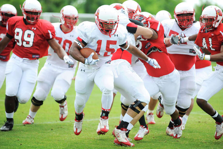 Lamar running back Cornelius Shackelford, center, rushes against the Lamar defense during the Cardinals final spring scrimmage. Lamar Soccer Complex, Saturday, April 10, 2010.   Valentino Mauricio/The Enterprise