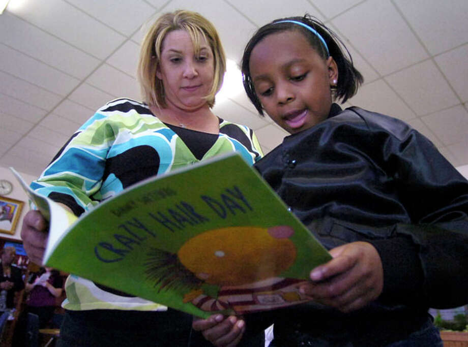 Jackie Wiltz, left, the RIF coordinator and reading coach at Dunbar Elementary School, listens to Jazaleen Broussard read out loud after a small book distribution in the school library. Dave Ryan/The Enterprise