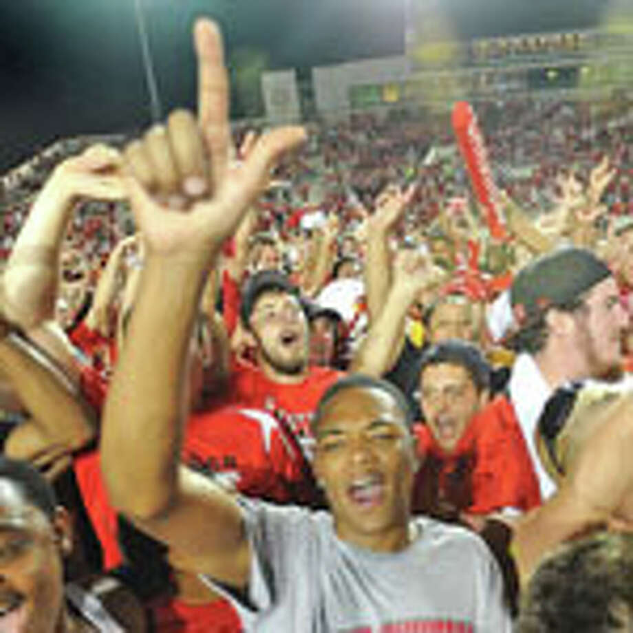Lamar students rush the field after the Cardinals beat the Warriors 21 to 14 in the university's first home football game in more than 20 years. Guiseppe Barranco/The Enterprise