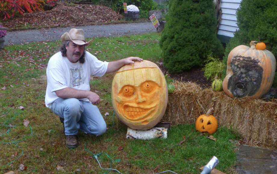 Wyatt Whiteman, of Stillson Road, poses with a giant pumpkin that he sculpted into a face. Photo: Tom Cleary / Fairfield Citizen