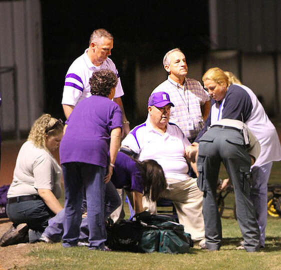Paramedics and emergency crew members tend to Newton Football Coach Curtis Barbay after he passed ou