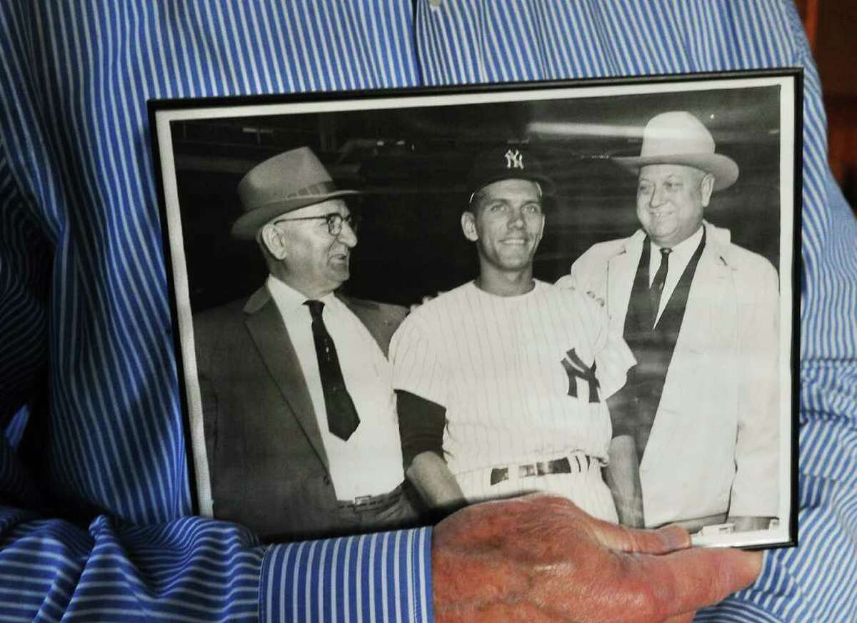 Phil Linz, former teammate of Mickey Mantle, holds a picture of himself with his father Ben Linz, on left, and his mentor Sheriff Fowble, on right, taken in April 1962 on opening day at Yankee Stadium. He sits with the photo in his family room in Stamford, Conn. on Thursday October 28, 2010.