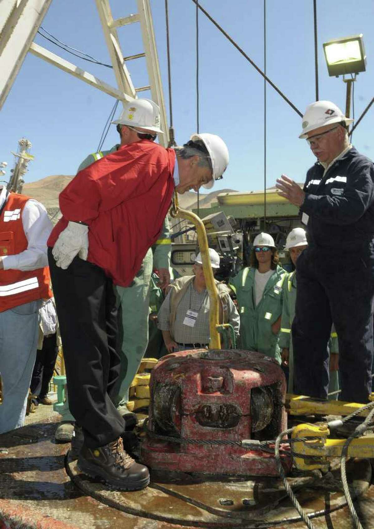 In this picture released by Chile's Presidential press Office, Chile's President Sebastian Pinera, left, looks down where the drill that is being used for Plan