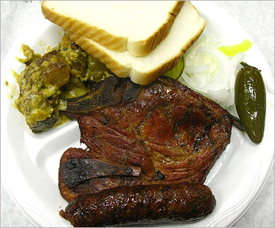 The pork steak at Gonzales Food Market is served with sausage and warm potato salad.
