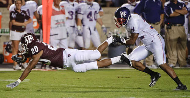 Texas A&M's Bradley Stephens (20) dives past Stephen F. Austin's Delano King for a first down on Sept. 4. The Aggies rushed for 192 yards in the season opener.