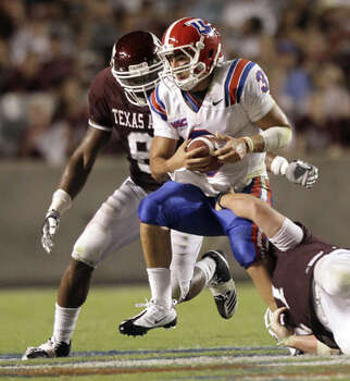 Texas A&M's Lucas Patterson (right) and Garrick Williams bring down Louisiana Tech quarterback Tarik Hakmi in the third quarter on Sept. 11. The Aggies held Tech to 269 yards, including just 61 rushing. A&M ranks fifth nationally allowing just 46 rushing yards a game after two games.
