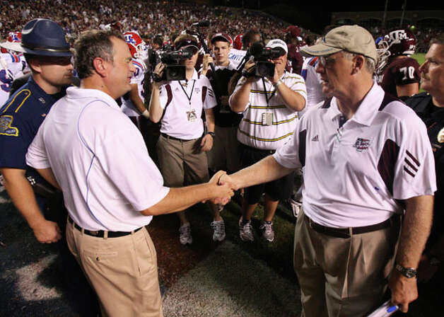 Louisiana Tech coach Sonny Dykes (left) shakes hands with Texas A&M coach Mike Sherman after the Aggies' 48-16 win over the Bulldogs on Sept. 11. / © 2010 Houston Chronicle