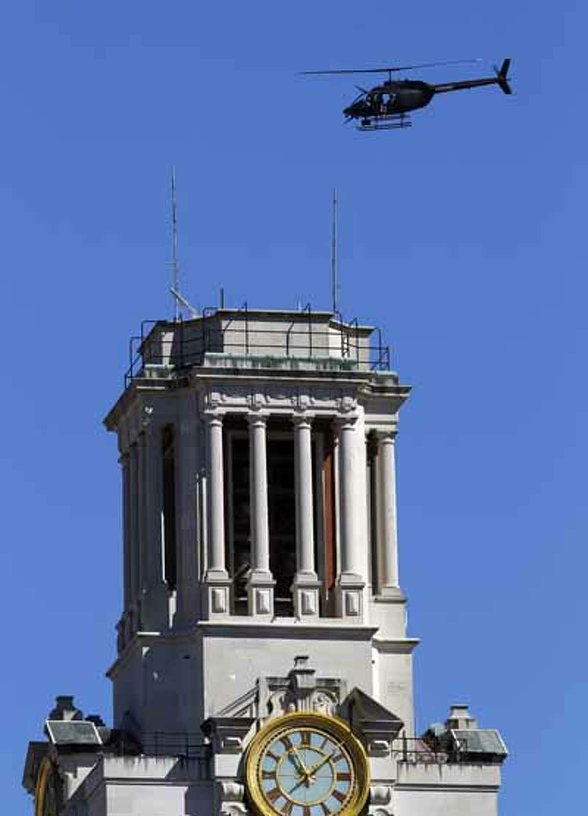 A police helicopter flies over the University of Texas clock tower. Helicopters flew back and forth over the campus, which was closed with police barricades and yellow crime scene tape stretched from buildings, trees and light poles blocking off access to campus.