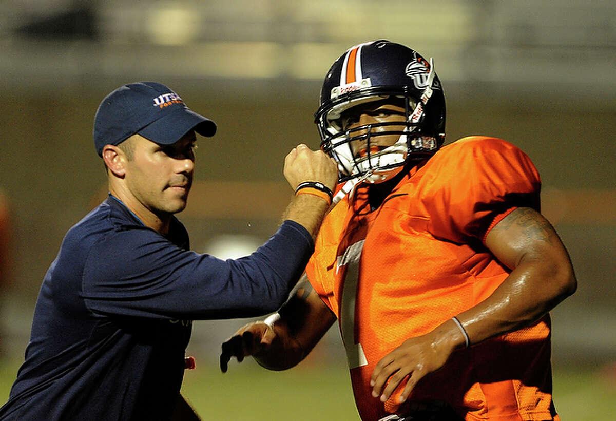 Assistant coach Travis Bush helps Kam Jones during practice.