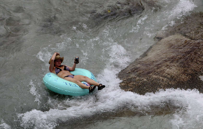 A woman slips past the tube chute on the Comal River in Prince Solms Park on Labor Day in New Braunf