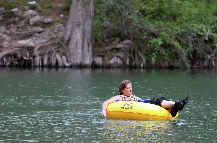 Sylvia Gonzales floats along the Guadalupe River at Camp Huaco Springs on Labor Day near New Braunfels, Texas. / San Antonio Express-News