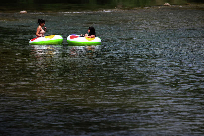Two individuals relax while floating along the Guadalupe River.