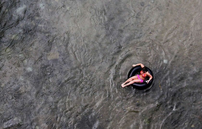 An individual floats amidst raindrops in the Comal River at Prince Solms Park in New Braunfels, Texa