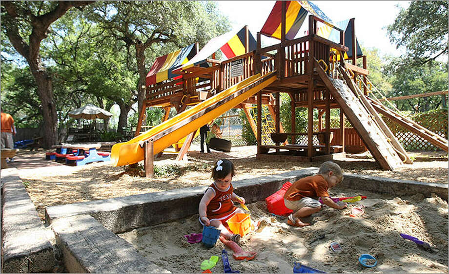 Sadie (left) and Walker Thetford play in the sandbox at Two Bros. BBQ Market, which has a large playscape where little ones can romp between bites.