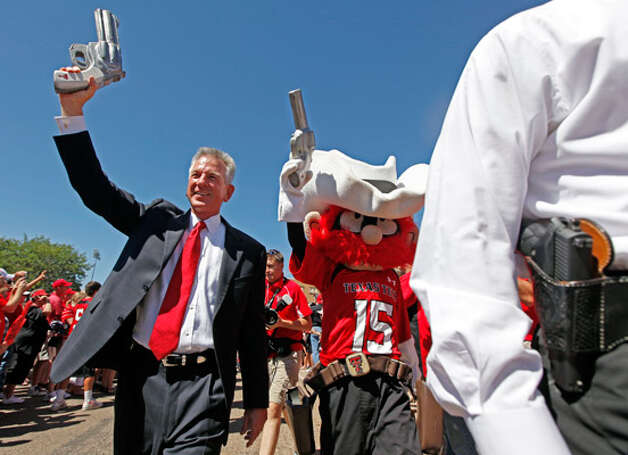 Coach Tommy Tuberville points one of Raider Red?s guns in the air at the first ?Raider Walk? before Tech beat SMU.