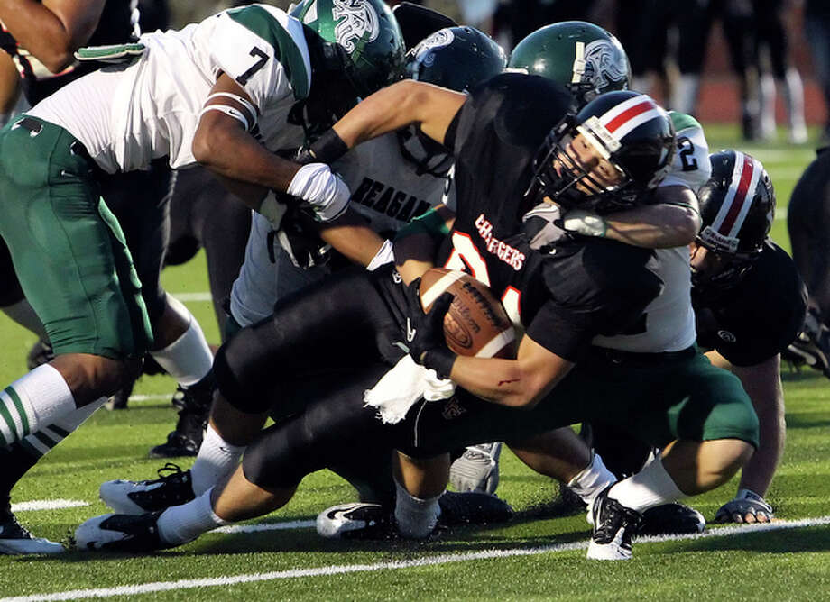 Churchill's Kenny Kilgore (center) plows his way in for the game's first touchdown against Reagan at Heroes Stadium on Friday, Sept. 24, 2010. / San Antonio Express-News