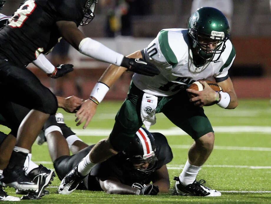Reagan quarterback Trevor Knight (10) attempt to evade tackles by Churchill. / San Antonio Express-News