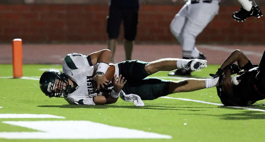 Reagan's Trevor Knight scores on a quarterback keeper to take a one-point lead against Churchill in the fourth, 14-13. / San Antonio Express-News