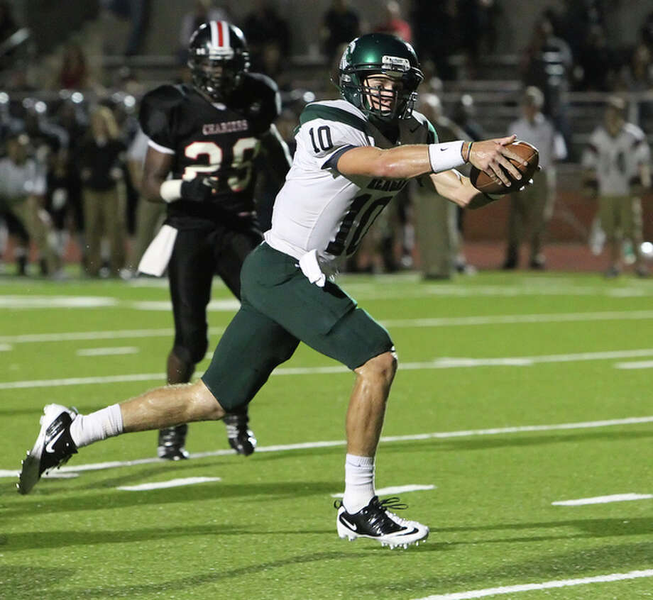Reagan quarterback Trevor Knight (10) runs in again and extends to score the go-ahead touchdown in the second overtime against Churchill, 35-28. / San Antonio Express-News