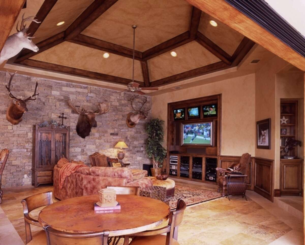 This man cave includes a poker table, stone wall and a built-in entertainment center.
