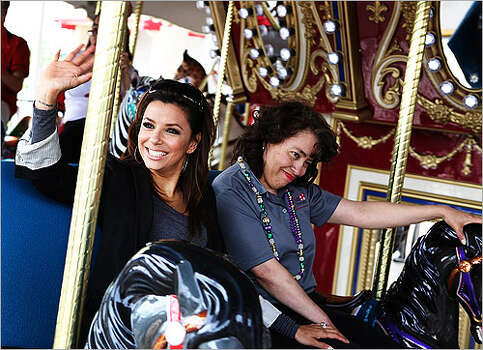 Eva Longoria Parker rides a carousel with her sister, Lisa, to whom she credits the inspiration behind her Eva's Heroes organization, which helps developmentally disabled children and young adults.