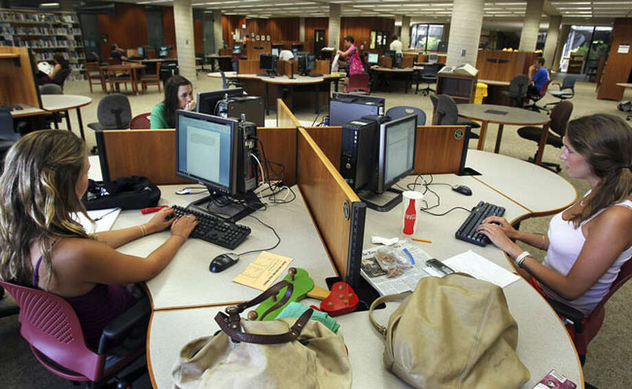 Andree Gonzalez (from left), Moira Bedel and Hannah Harms occupy a computer table at Trinity University's Coates Library last week. While traditional research areas at the library are almost vacant, students use computers for study there.