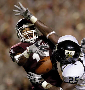 Texas A&M wide receiver Terrence McCoy (11) makes the game-tying  touchdown catch in the fourth quarter as Florida International's  Jonathan Cyprien (25) defends during the fourth quarter on Sept. 18. / AP