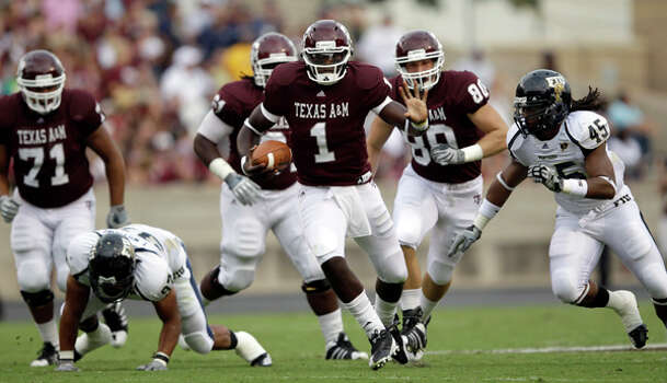 Texas A&M quarterback Jerrod Johnson (1) rushes for a gain as Florida International's Aaron Davis (45) gives chase during the first quarter on Sept. 18. Because he was sacked six times for 36 yards in losses, Johnson was held to 3 yards rushing. / AP