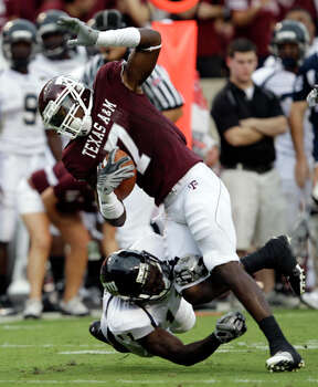 Texas A&M wide receiver Uzoma Nwachukwu (7) catches a pass for a first down as Florida International's Ashlyn Parker (11) tackles him on Sept. 18. Nwachukwu had just the one catch for 18 yards. / AP