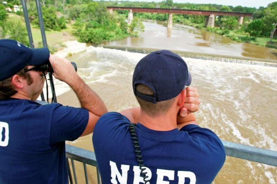 New Braunfels firefighters Brent Bayliss (left) and Chris Sheppard watch the hydraulic current as friends and family members wait as the search continues for the bodies of two swimmers who dived into the Guadalupe River during flood conditions from a railroad bridge in New Braunfels.