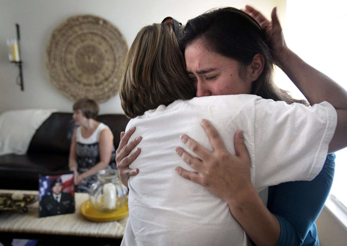 Gabriela Montoya (right), whose brother Diego Montoya was recently killed in action, is comforted by her aunt Liza Balderas of Mission. Rosie Guerra, Diego's mother, sits on the sofa with a portrait of her son. Family members of Diego Montoya, a graduate of Taft High School, gather at their home to support each other.