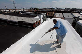 James Peterson with Bio Neighbors applies a coating of Acrymax to the roof of a row home in Philadelphia.