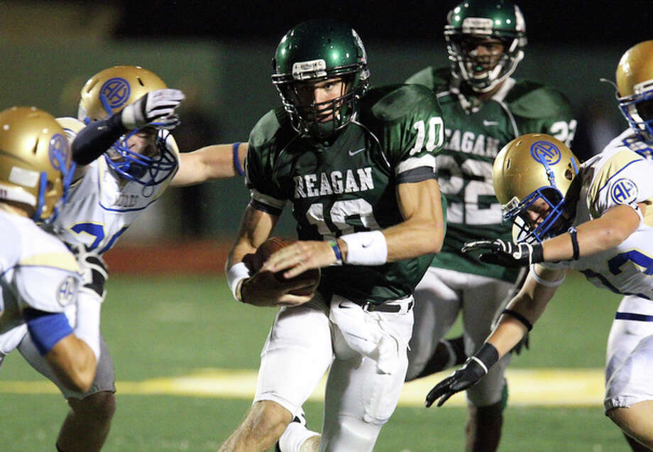 Reagan quarterback Trevor Knight (11) runs between a trio of Alamo Heights defenders. / San Antonio Express-News