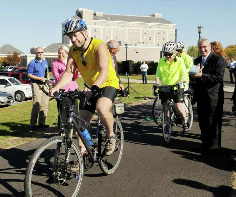 Cyclist Howard Halstead of Schenectady, a member of the Friends of The Mohawk-Hudson Bike-Hike Trail, rides through the freshly cut ceremonial ribbon by dignitaries including Assemblyman James Tedisco, at right, to announce the completion of a four-mile section of the Erie Canalway Trail/Mohawk-Hudson Bike-Hike Trail in Schenectady on Thursday, Oct. 28, 2010.  The trail, rebuilt with federal stimulus funds, is between Washington Avenue in Schenectady and Route 146 in Niskayuna.  It is part of the 35-mile bike-hike Canalway Trail between Albany and Rotterdam Junction.  (Luanne M. Ferris / Times Union ) Photo: Luanne M. Ferris