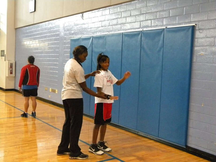 WNBA guard Marie Ferdinand explains the importance of motion during a recent basketball skills camp.