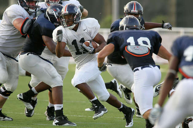 Running back David Glasco (11) bursts through a trio a defenders. / San Antonio Express-News