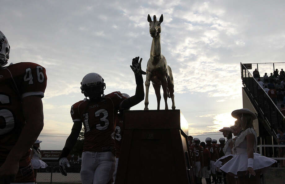 Madison players touch the statue of the Maverick horse as part of tradition before they take the field against Kerrville Tivy in football at Comalander Stadium on Friday, Sept. 3, 2010. / San Antonio Express-News