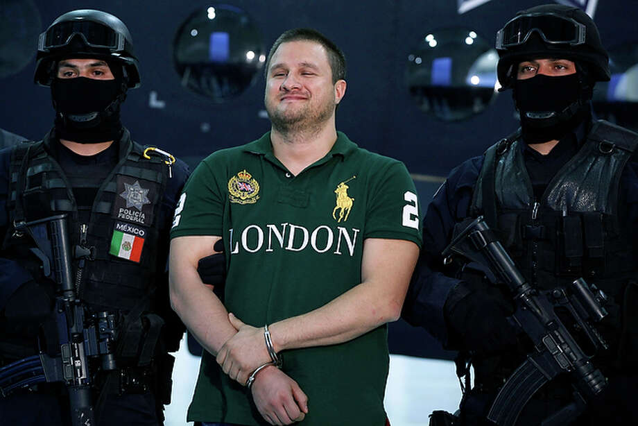 "Federal Police escort Texas-born fugitive Edgar Valdez Villarreal, alias ""the Barbie,"" center, during his presentation to the press in Mexico City, Tuesday Aug. 31, 2010. (AP Photo/Alexandre Meneghini) / AP"