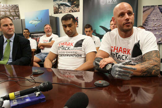 Shark attack survivor Paul de Gelder of Sydney (right) speaks as fellow shark attack survivor Achmat Hassiem of Cape Town, South Africa (front center), Matt Rand, director of the Pew Environment Group's Global Shark Conservation Campaign (left), and shark attack survivors seated behind them listen during a news conference Monday in New York, urging the United Nations to adopt measures to protect sharks. De Gelder lost his right hand and right lower leg when he was attacked by a shark.